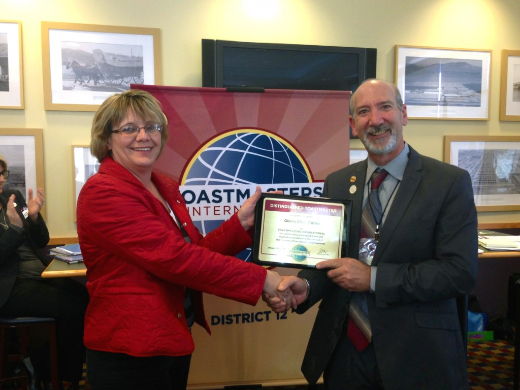 Gloria Golike is presented with the Distinguished Toastmasters award by Michael Osur, Toastmasters District 12 Governor.