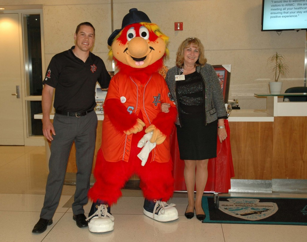 (Left to right) Joe Hudson, Inland Empire 66ers general manager, and Pat Redinger, ARMC volunteer services coordinator, stand beside Inland Empire 66ers mascot, Bernie, before he visits children in the Pediatrics Unit at Arrowhead Regional Medical Center on May 8. Bernie visited the hospital to help kick off a baseball Fundraiser Night, which is being held on June 28 at San Manuel Stadium in San Bernardino. The event, hosted by ARMC's Volunteer Auxiliary and the Inland Empire 66ers, will help raise funds for a new state-of-the-art diagnostic tool for ARMC's Breathmobile® program
