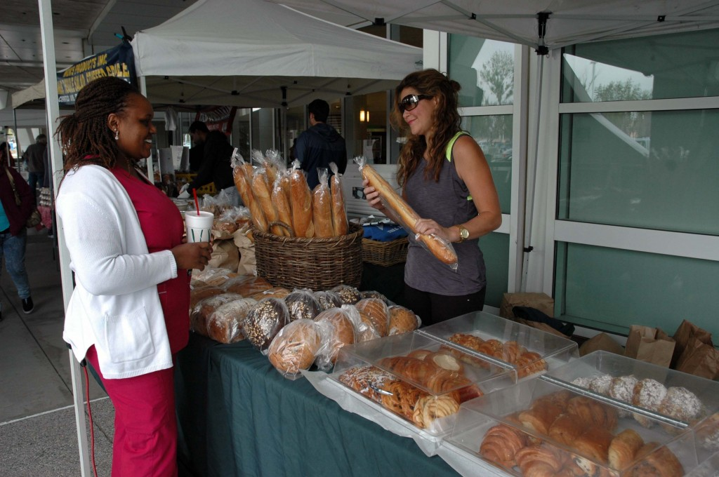 ARMC Nurse, Stella Kirai, visits a baked goods booth on Wednesday at Arrowhead Regional Medical Center's new Farmers Market outside the main hospital entrance. Approximately 800 staff, patients and visitors browsed among 14 booths, which offered fresh fruit, vegetables, honey, olive oil and other items for purchase. The Farmers Market is part of ARMC's ongoing commitment to health and wellness.