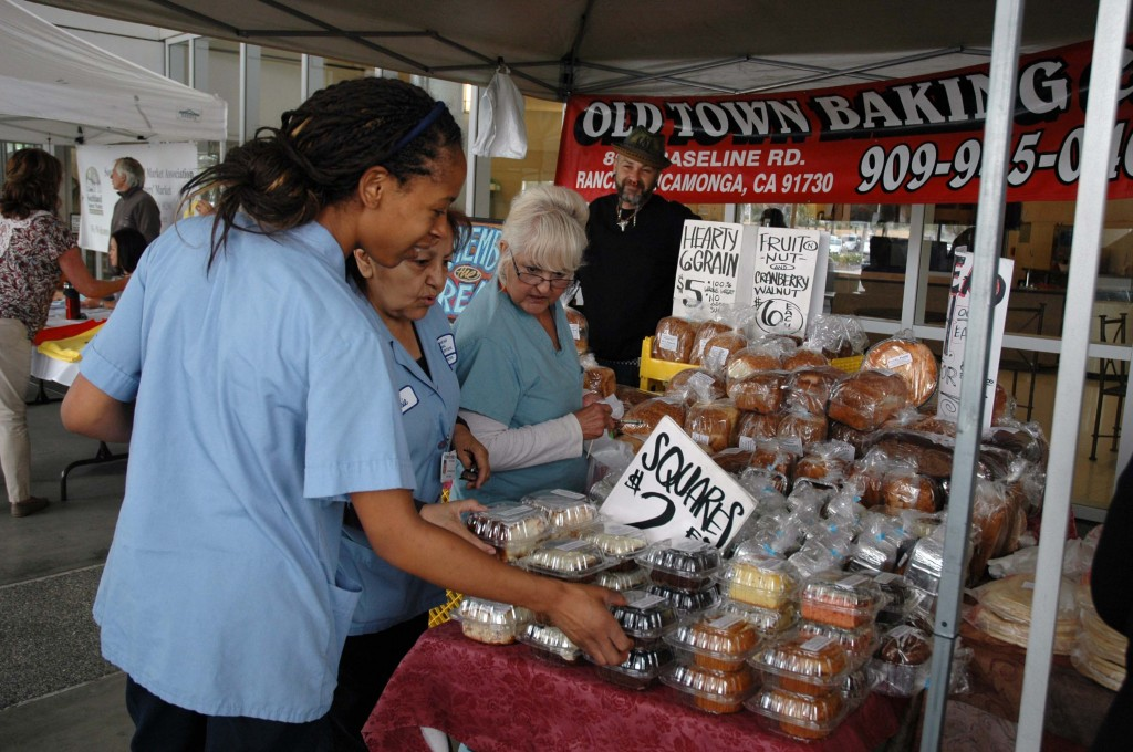 Arrowhead Regional Medical Center Environmental Services Department employees (left to right) Rekeila Anderson, Rosie Gomez, and Virginia Contreras, survey the baked goods at Wednesday's new Farmers Market outside the main hospital entrance. Approximately 800 staff, patients and visitors browsed among 14 booths, which offered fresh fruit, vegetables, honey, olive oil and other items for purchase. The Farmers Market is part of ARMC's ongoing commitment to health and wellness.