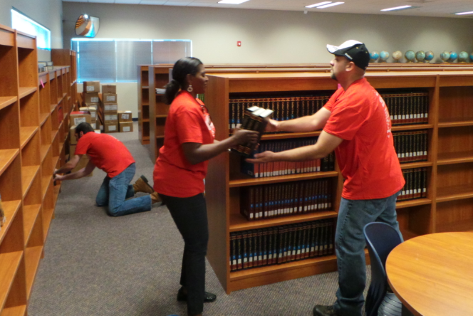 Volunteers, Colletee Combre and Esteban Castro work to make the library at the Cobalt Institute of Math & Science in Victorville a usable space for students. The initiative is part of Verizon's pledge to give back to the Southern California communities it serves.