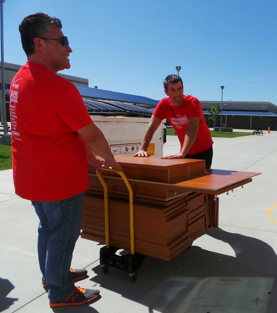Cesar Hakim (left) and Mike Washburn (right), volunteers with Verizon FiOS, loading in new tables for the library at the Cobalt Institute of Math & Science in Victorville.  The initiative is part of Verizon's pledge to give back to the Southern California communities it serves.