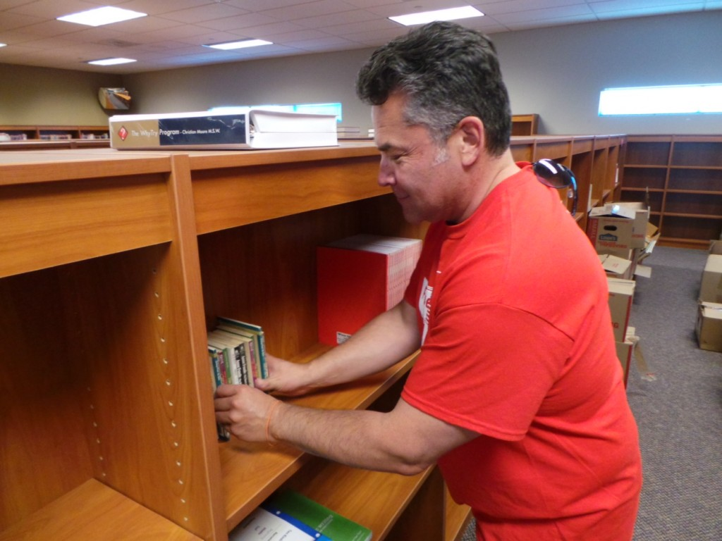 Cesar Hakim, a volunteer from Verizon FiOS, organizing books at the Cobalt Institute of Math & Science in Victorville.  The initiative is part of Verizon's pledge to give back to the Southern California communities it serves.