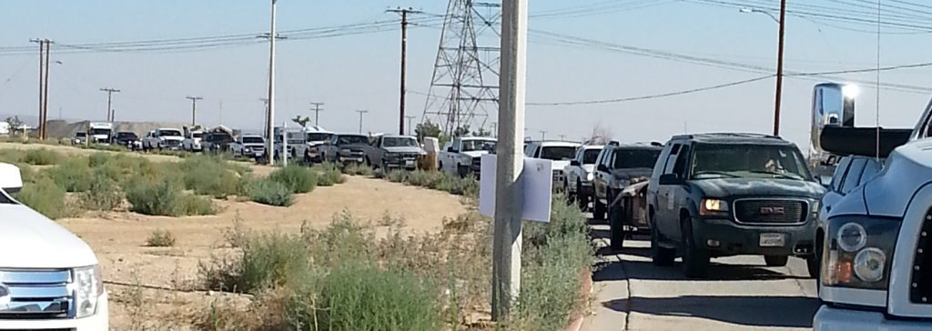 Residents line-up to drop off trash and debris at Adelanto Stadium